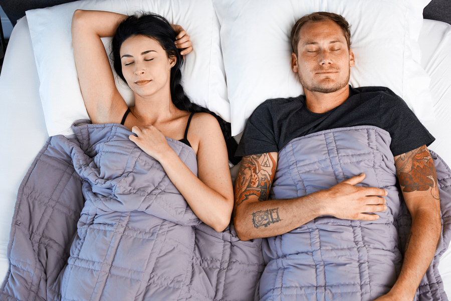 Couple Sleeping in bed under Moonbow Cooling Weighted Blanket