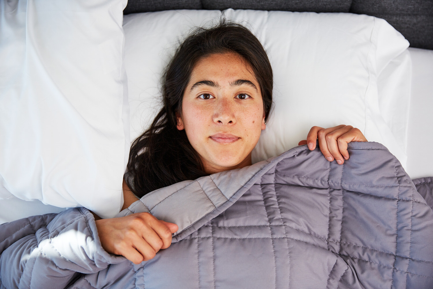 Woman awake in bed under Moonbow Cooling Weighted Blanket