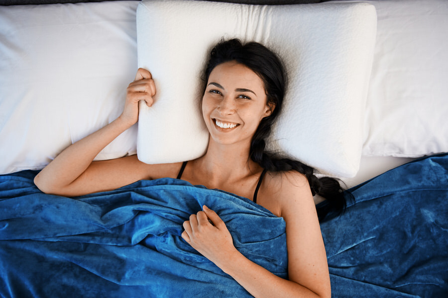 Woman Smiling Under Moonbow Cooling Weighted Blanket with Blue Duvet Cover