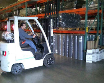 Man driving a white forklift in a Rubber-Cal Warehouse