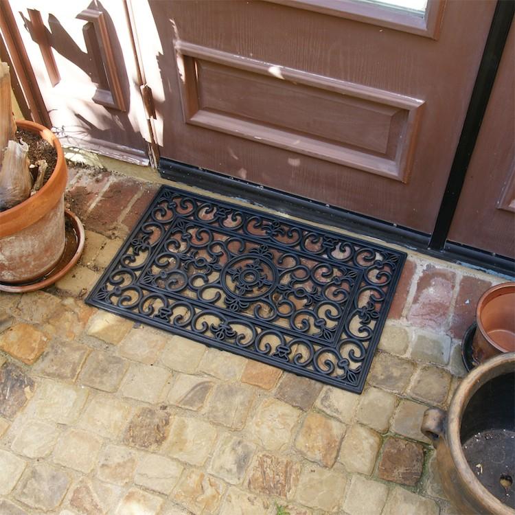 Blooming flowers doormat outside of doors on brick floor