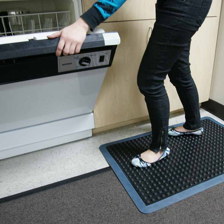 person doing dishes while standing on bubble top anti-fatigue mat