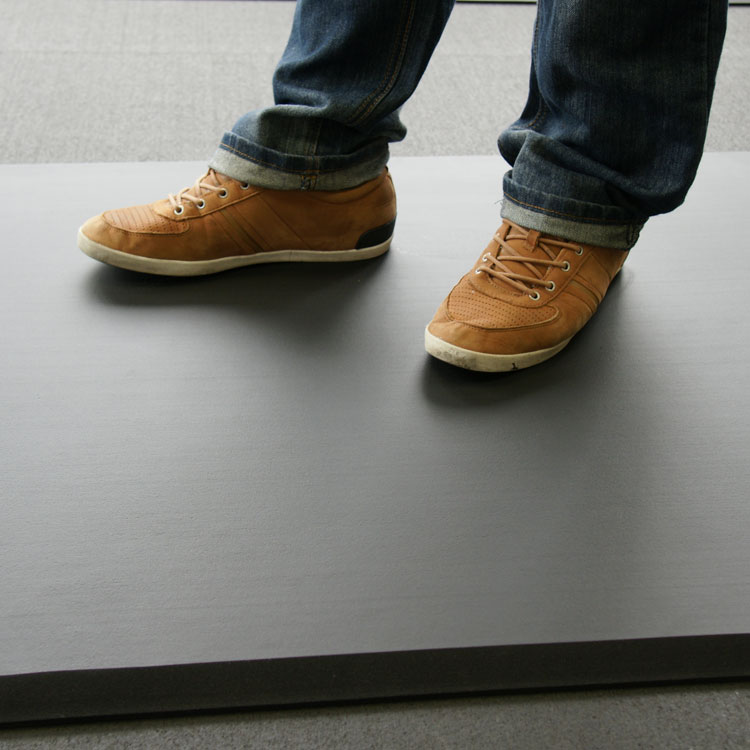 person with brown shoes standing on black comfort foam cloud mat