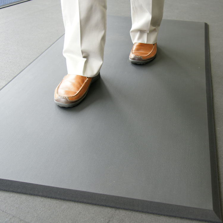 person with brown leather shoes walking on black comfort cloud mat