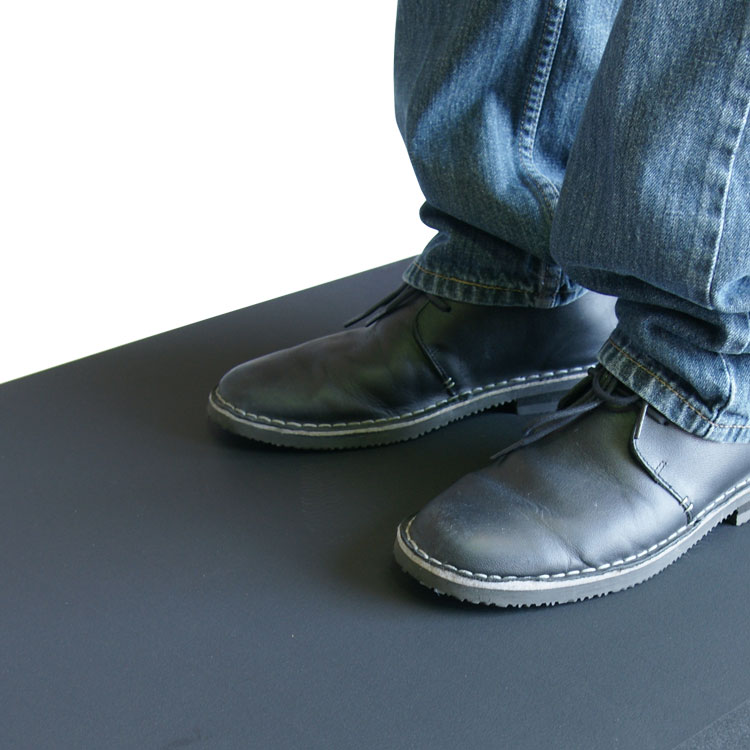 person with black leather shoes standing on top comfort cloud mat