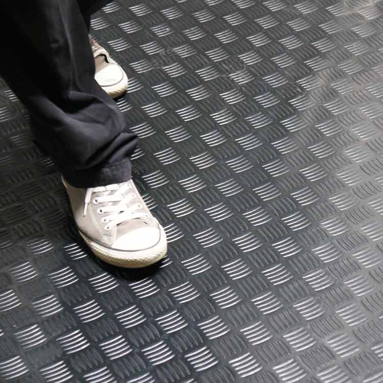 person with converse shoes walking on diamond grip pvc roll flooring