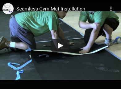 Two people setting up a rubber mat floor