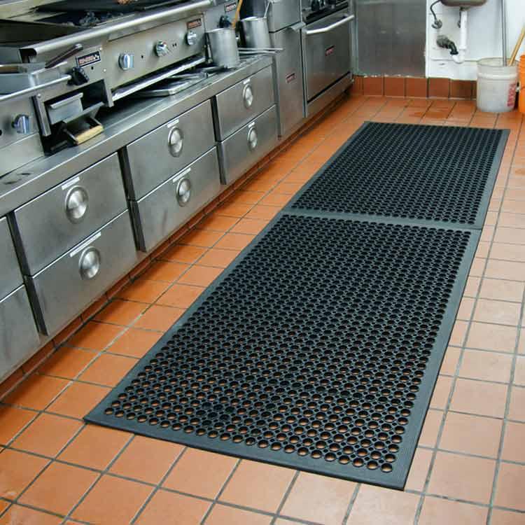 Black Dura-Chef mat in a commercial kitchen on orange tile