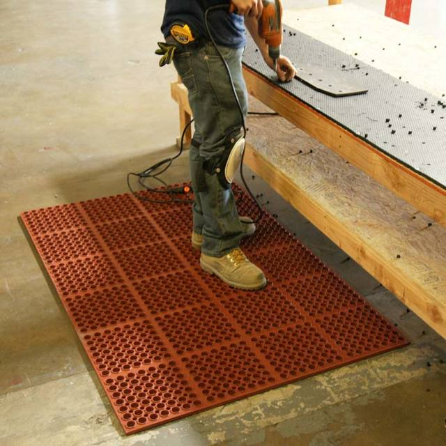 Person using work bench while standing on Red Dura Chef Anti-Fatigue Mat