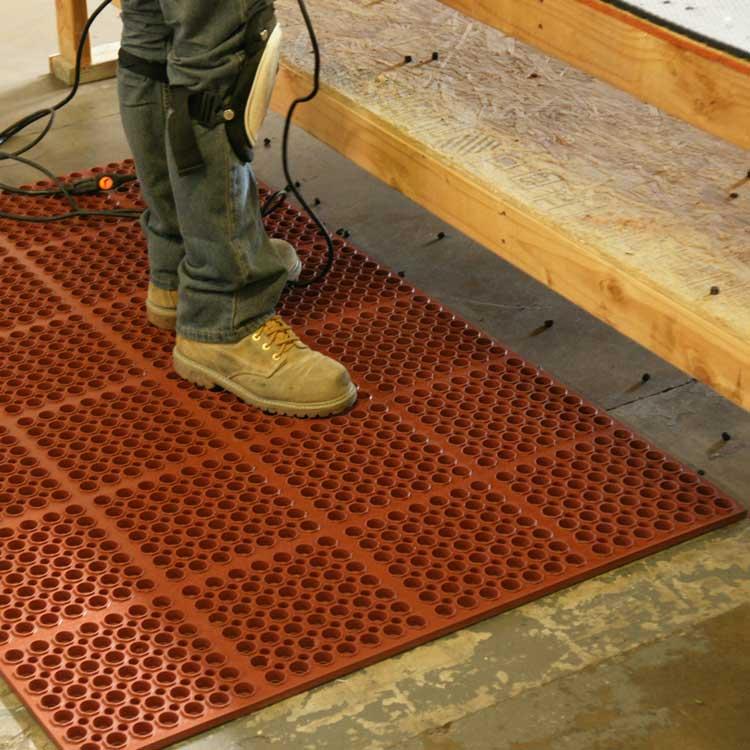 person standing Orange Dura-Chef anti-fatigue kitchen mat in a warehouse