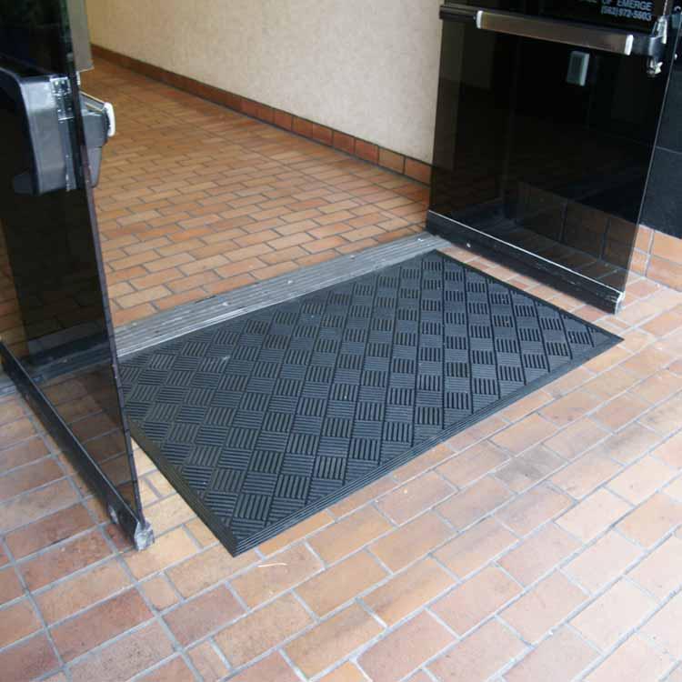 Checkered Dura-Scraper on brick floor near in front of open doors.