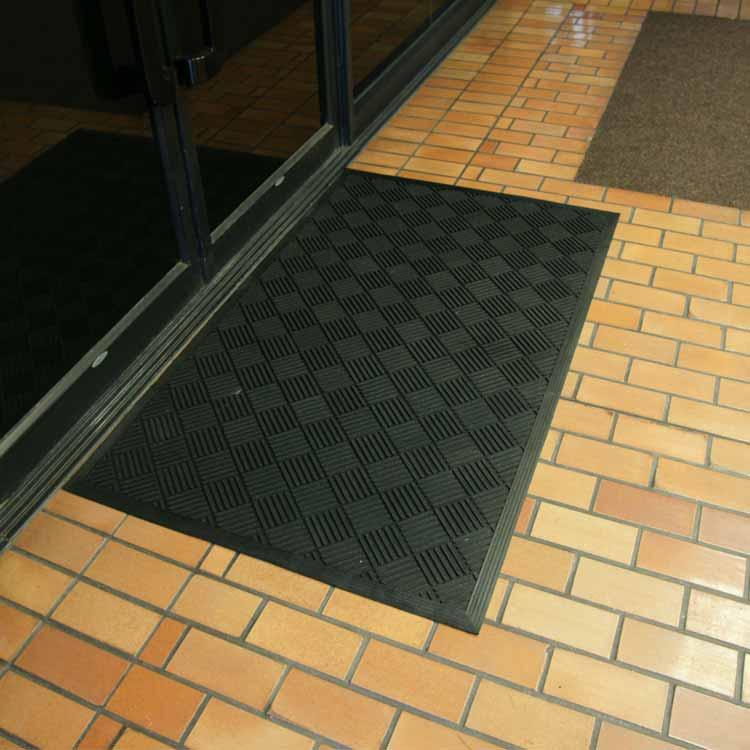Black Dura Scraper Checkered Doormat on brick floor outside doors
