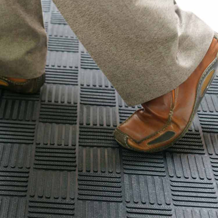 person wearing brown shoes walking on black dura scraper checkered doormat