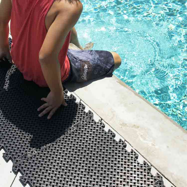 Person sitting on Eco-Drain Rubber my with his feet in the pool
