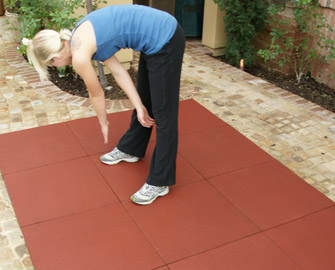 Woman stretching on red Eco-Sport tiles outside