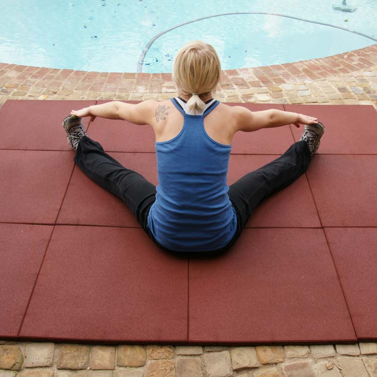 Woman stretching on Red Eco-Sport Floor near pool