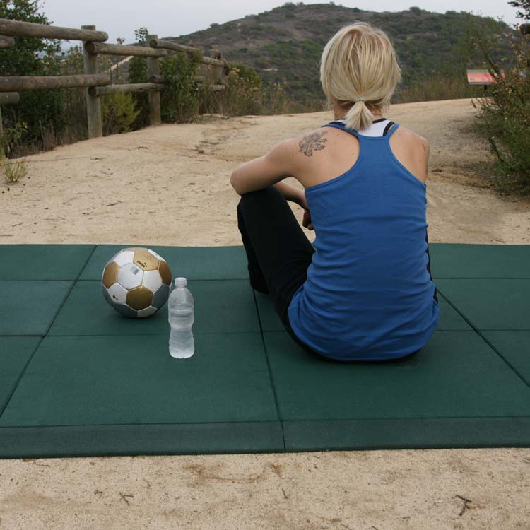 Woman mediating on the green eco sport mat outside