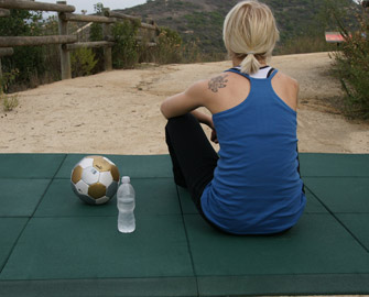 Person preparing to practice yoga on Green Eco Sport Tiles behind a wooden fence