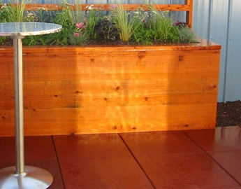 Red Eco-Sport Rubber Tile in patio area near a wooden planter