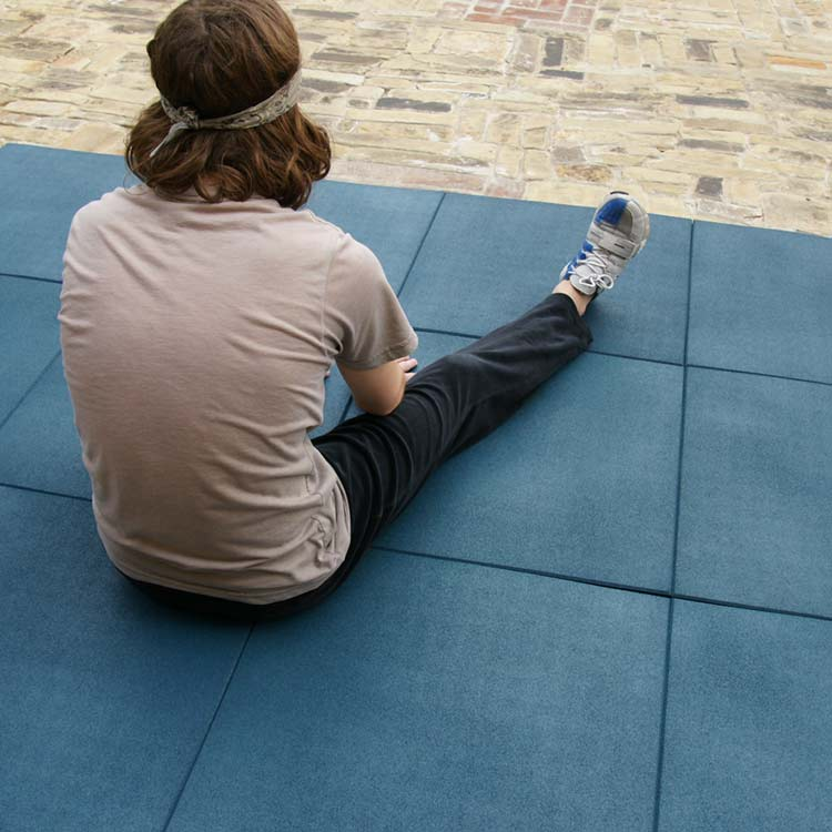 Person ready to stretch sitting on a blue eco-sport tile floor