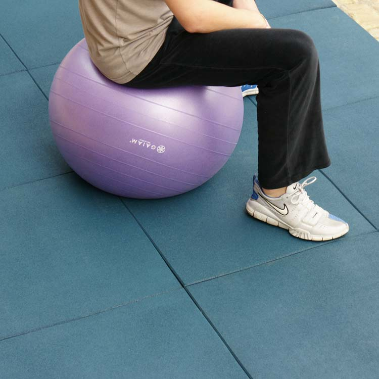 Blue Eco-Sport tile floor with person sitting on an exercise ball preparing to exercise