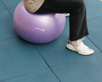 Blue Eco-sport interlocked tiles under a person using a purple exercise ball