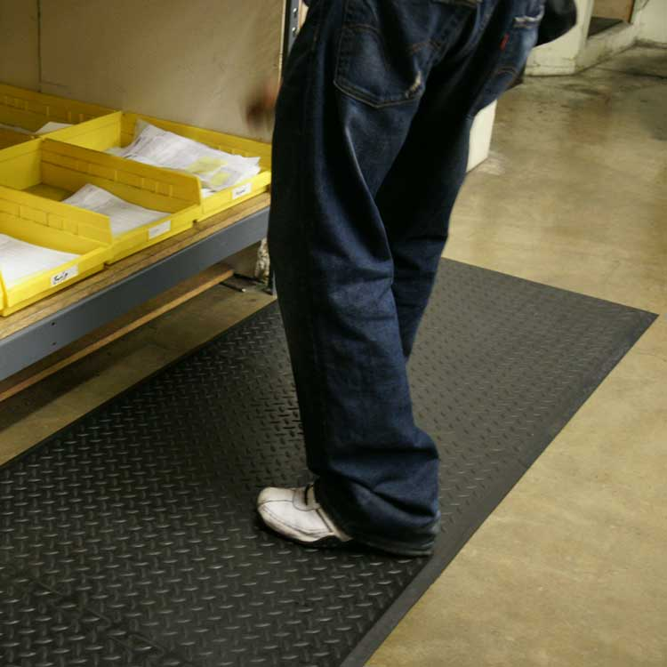 person standing on black foot rest anti-fatigue mat in a warehouse