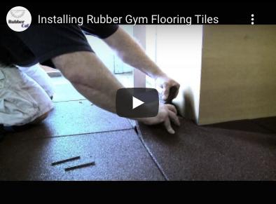 A person setting a cut rubber tile around a corner