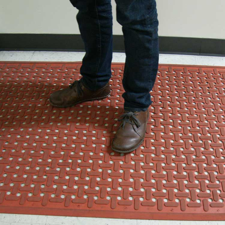 Person wearing brown shoes while standing on Red Kitchen Mat