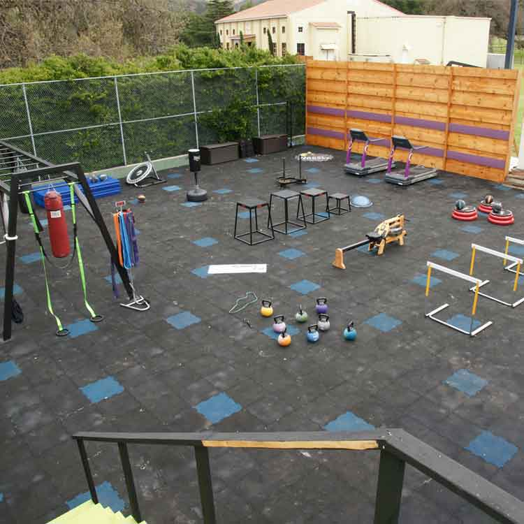 Hurdles and other gym equipment on recycled rubber tile floors