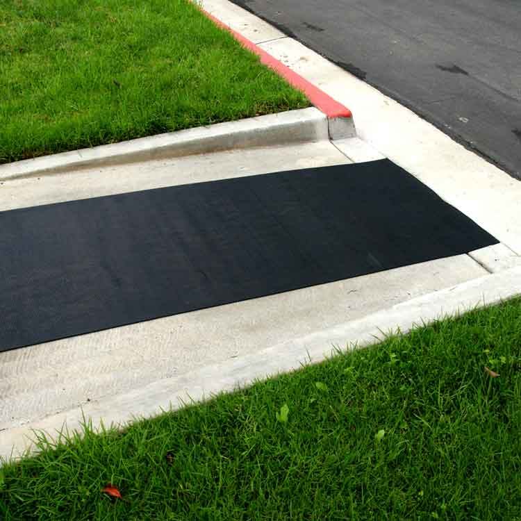 Ramp Cleat Rubber Mat leading down a cement ramp near grass and a curb