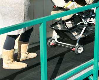 Woman pushing a stroller up ramp that is covered with ramp cleat rubber mat