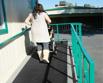 Woman pushing a stroller up a ramp with a Ramp-cleat mat