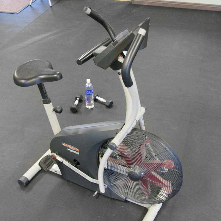 Exercise Bike and dumbbells on recycled rubber floor