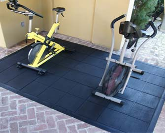 Different colored exercise bikes on interlocking rubber tile