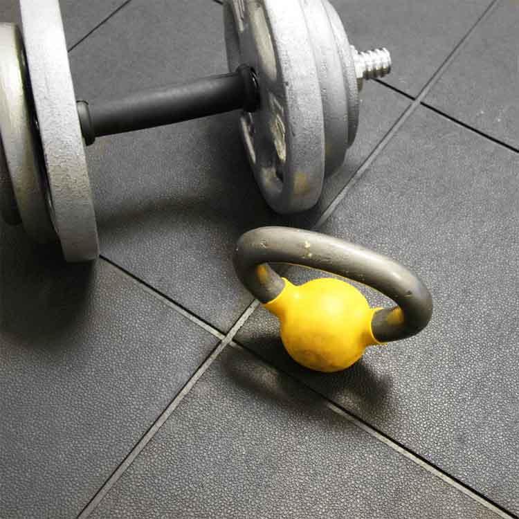 Black Revolution Flooring tiles under dumbbell and kettlebell for workout
