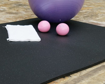 Shark Tooth Mat under a purple exercise ball and 2 weighted pink balls