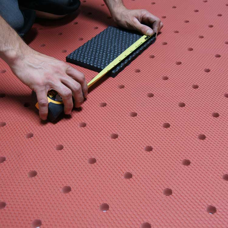 person measuring mat on red soft cloud drainage mat