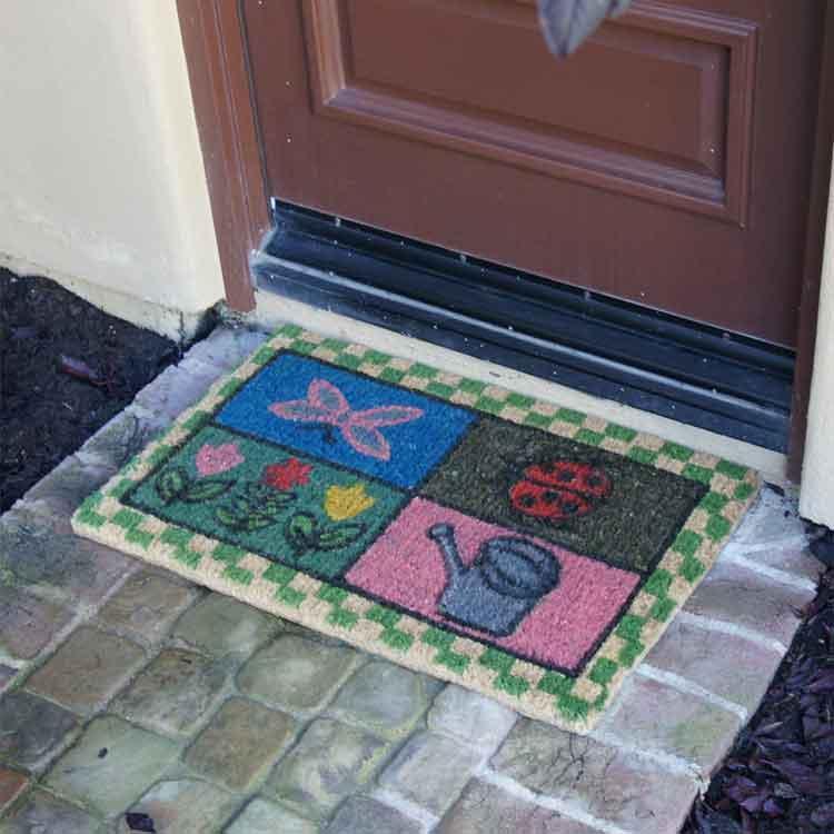 Patterned Doormat on brick outside of a door