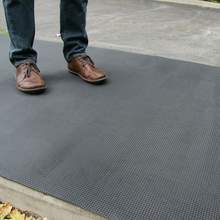 person standing on black super grip rubber mat outside