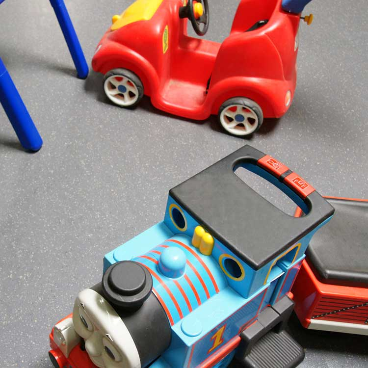 Plastic toy train and car on Terra Flex rubber floor in a playroom