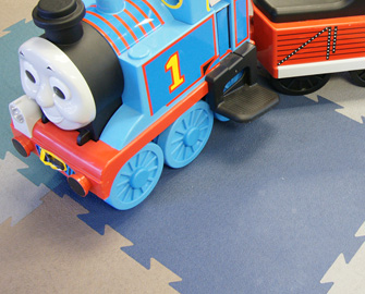Close-up of toy train on multiple Terra Flex tiles in each color