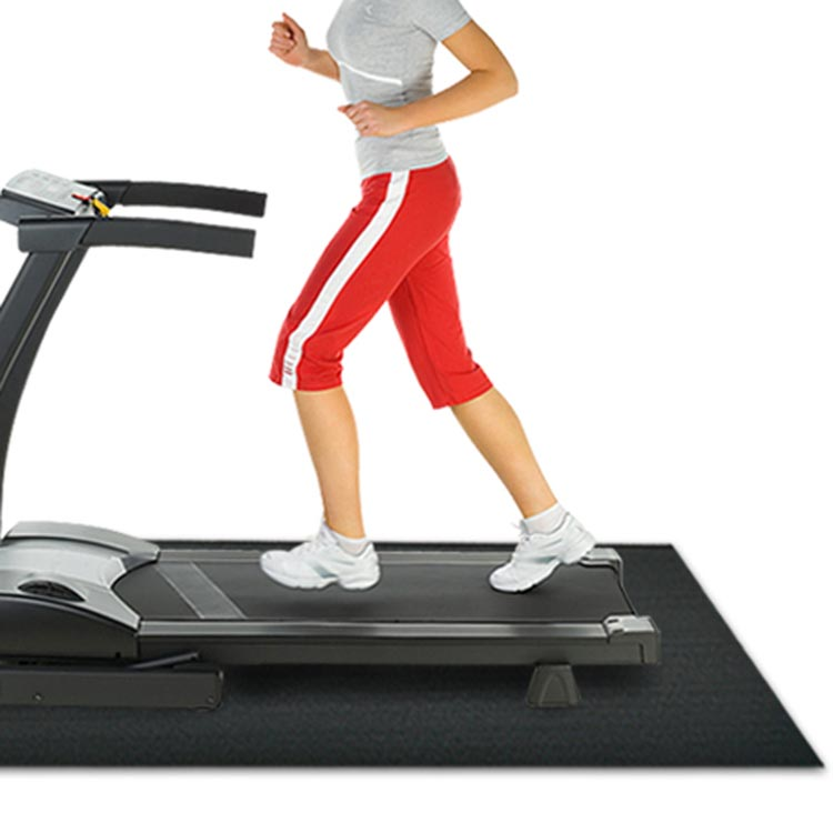 Woman running on a treadmill which is on a treadmill mat