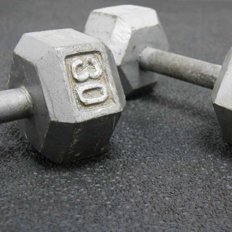 dumbbells laying on black tuff flex on gym floor