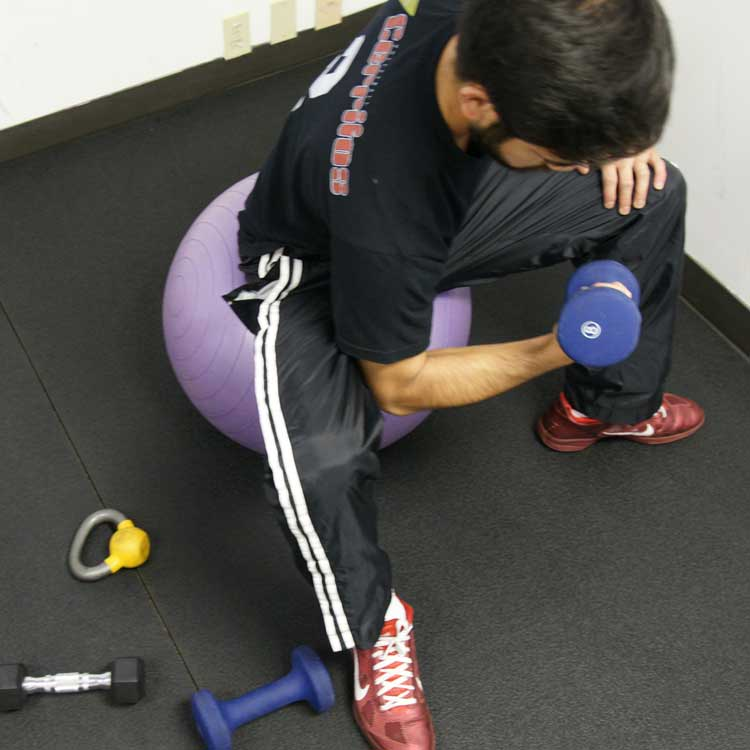 guy working out on a yoga ball in fitness room