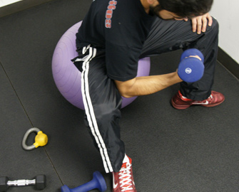 Tuff-Flex rubber floor under a man sitting on a purple exercise ball lifting a dumbbell