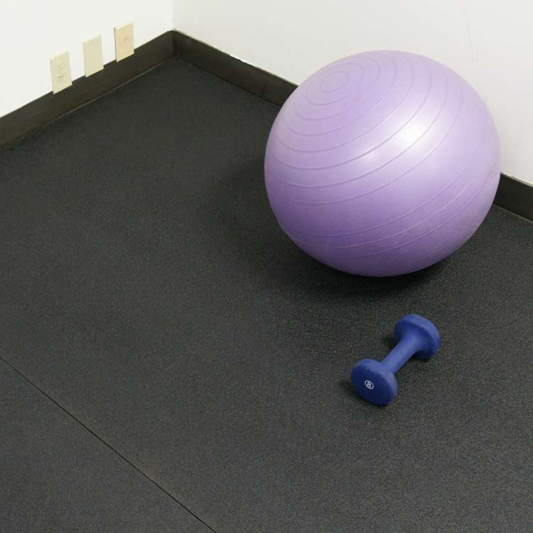 Exercise Ball near a dumb bell on recycled rubber flooring in a corner