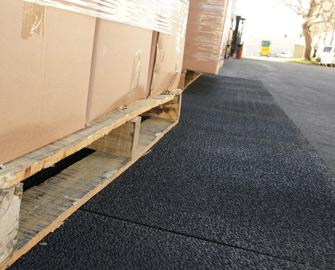 A Tuff Flex Rubber Mat on asphalt carrying a pallet