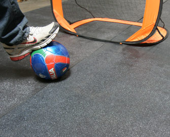 Person standing on a recycled rubber floor with a foot on a soccer ball in front of a net