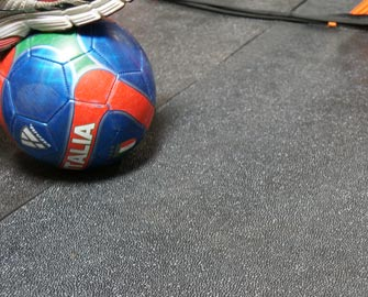 Close-up of stepping on soccer ball by net while on top of Tuff-N-Lastic Rubber Flooring